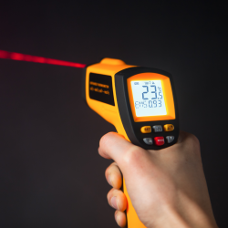 Hand holding a yellow infrared thermometer on a black backroung